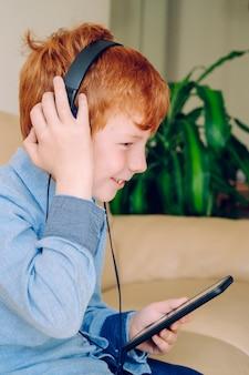 Ragazzino astuto che ascolta la musica con le cuffie insonorizzate del telefono cellulare a casa.