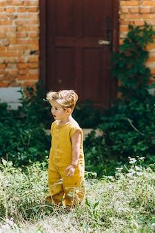 Ragazzino bello con capelli bianchi in una combinazione gialla sullo sfondo del muro