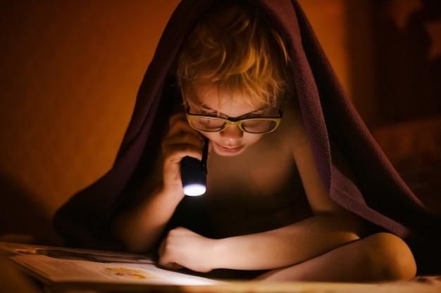 Ragazzino biondo 6-7 anni con gli occhiali che legge il libro sotto la coperta con la piccola torcia durante la notte oscura