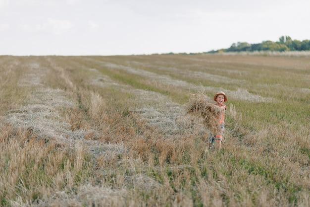 Ragazzino biondo che gioca fieno nel campo. estate, tempo soleggiato, agricoltura.