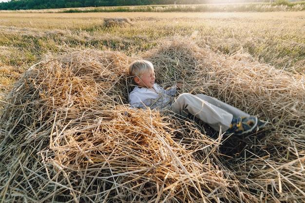 Ragazzino biondo divertendosi saltando sul fieno nel campo. estate, tempo soleggiato, agricoltura. infanzia felice. campagna.