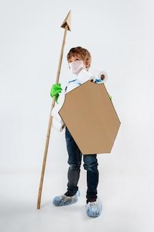 Ragazzino caucasico come un guerriero in lotta con la pandemia di coronavirus, con uno scudo, una lancia e una bandoliera di carta igienica, attaccando