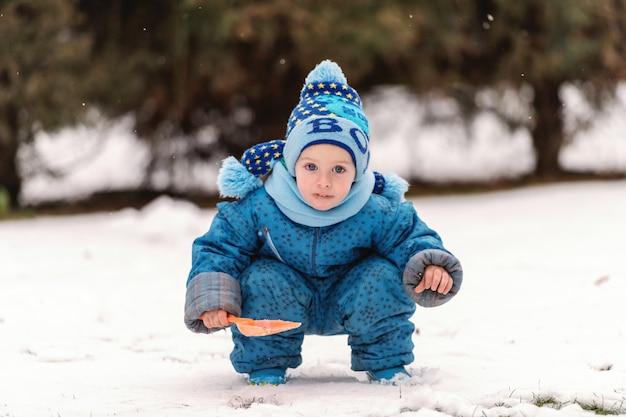 Ragazzino caucasico sveglio in vestiti caldi e con sciarpa e cappello che giocano sulla neve con la piccola pala.