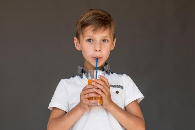 Ragazzino che beve il succo di arancia
