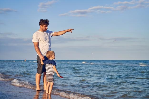 Ragazzino che cammina con il padre in spiaggia. estate