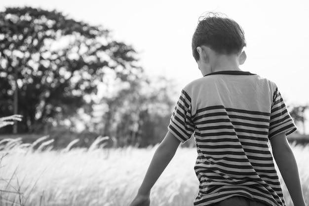 Ragazzino che cammina sul tramonto con campo di erbe dorate in bianco e nero