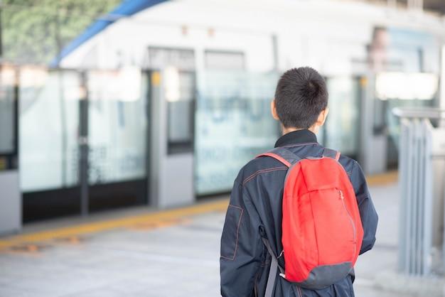Ragazzino che compra biglietto elettrico e che cammina nella stazione pubblica del treno di alianti con la famiglia