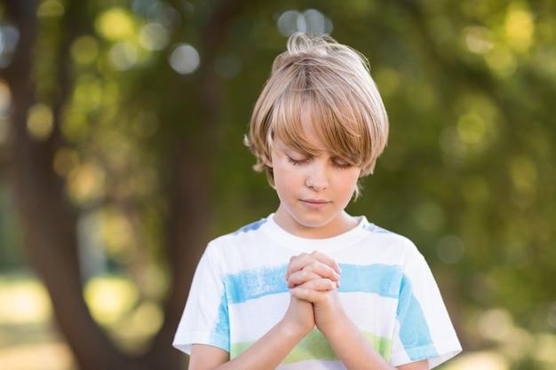 Ragazzino che dice le sue preghiere