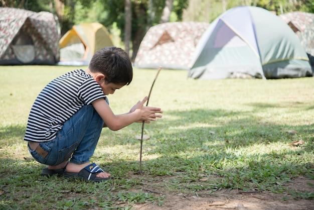 Ragazzino che fa un'attività all'aperto di estate di tenda della tenda del campo con la famiglia