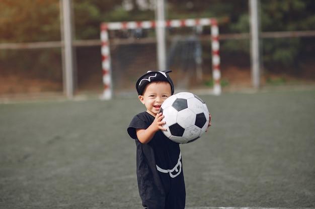 Ragazzino che gioca a calcio in un campo sportivo