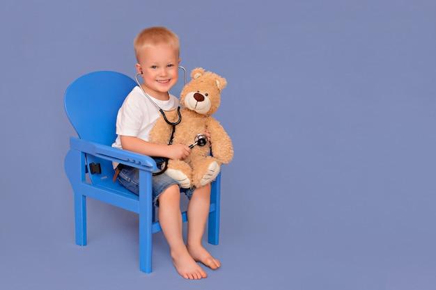 Ragazzino che gioca al dottore e che ascolta un orsacchiotto con uno stetoscopio su un fondo blu