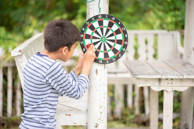Ragazzino che gioca attività all'aperto della famiglia del bordo delle freccette