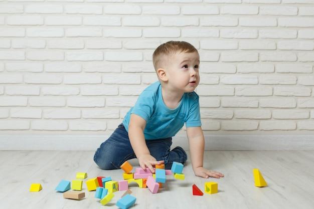 Ragazzino che gioca con il costruttore su fondo bianco. neonato che gioca i giocattoli dei blocchi