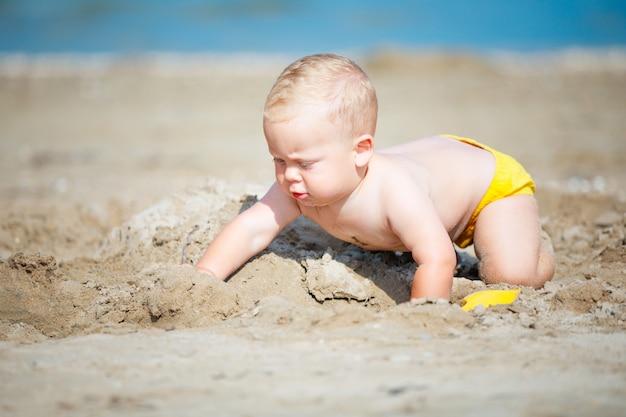 Ragazzino che gioca con la sabbia in riva al mare