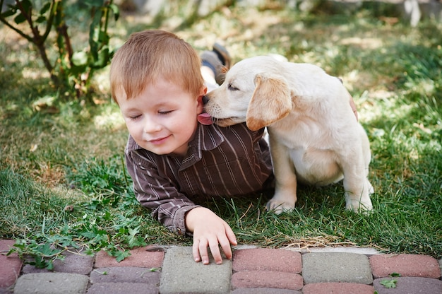 Ragazzino che gioca con un cucciolo di labrador bianco