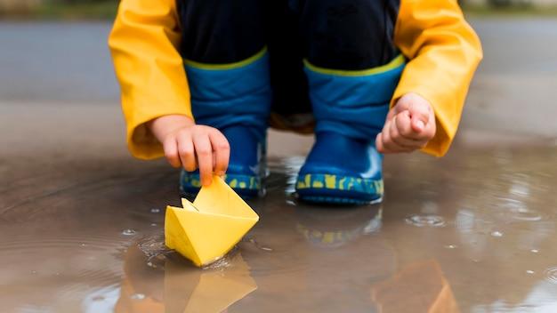 Ragazzino che gioca con un primo piano di barca di carta