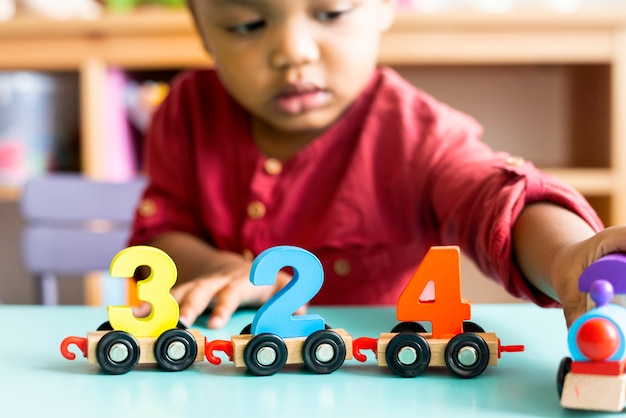 Ragazzino che gioca giocattolo di legno di matematica alla scuola materna