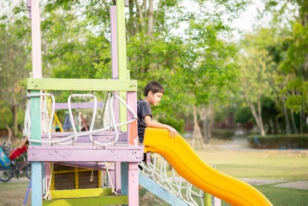 Ragazzino che gioca nel parco giochi all'aperto