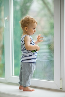 Ragazzino che guarda la pioggia attraverso la finestra