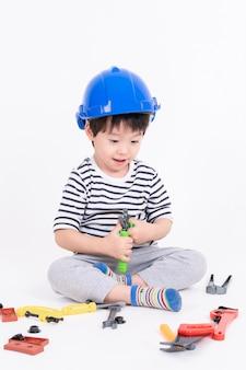 Ragazzino che indossa casco blu che si siede e che gioca con il giocattolo dell'attrezzatura per l'edilizia sul bianco