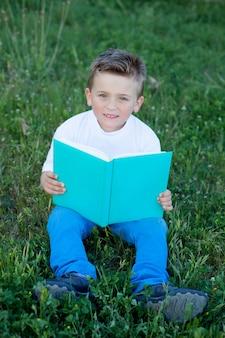 Ragazzino che legge un libro all'esterno