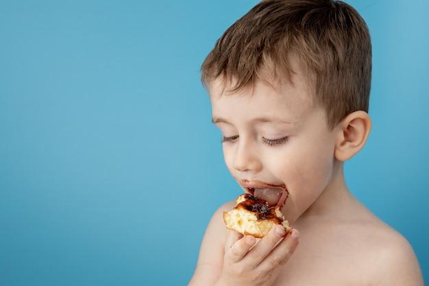 Ragazzino che mangia la ciambella al cioccolato. carino ragazzo felice spalmato di cioccolato intorno alla bocca. concetto di bambino, cibo gustoso per bambini