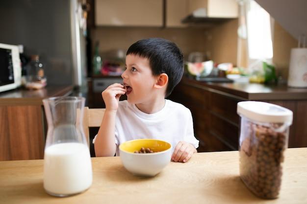 Ragazzino che mangia prima colazione a casa