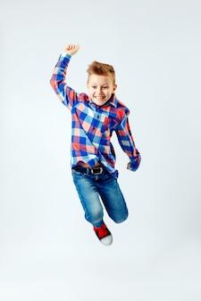 Ragazzino che salta nella colorata camicia a quadri, blue jeans, gumshoes. isolato.