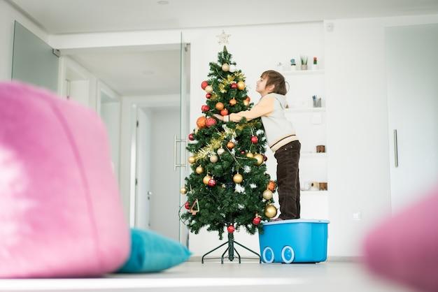 Ragazzino che si arrampica sulla scatola dei giocattoli per decorare l'albero di natale