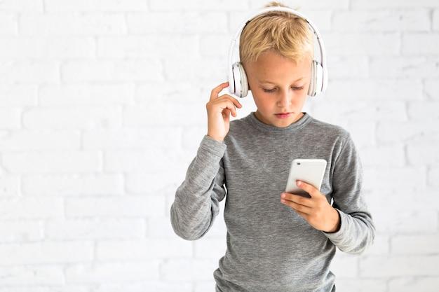Ragazzino che si diverte con smartphone e auricolari