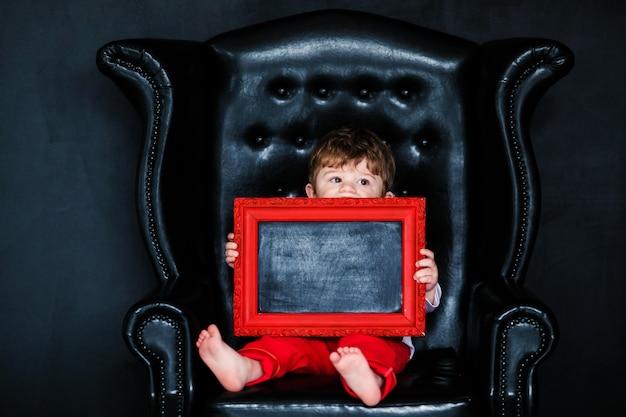 Ragazzino che si siede sulla poltrona con l'immagine incorniciata rossa sul giorno di biglietti di s. valentino