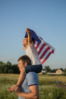 Ragazzino che tiene la bandiera americana nelle sue mani al vento sul campo verde