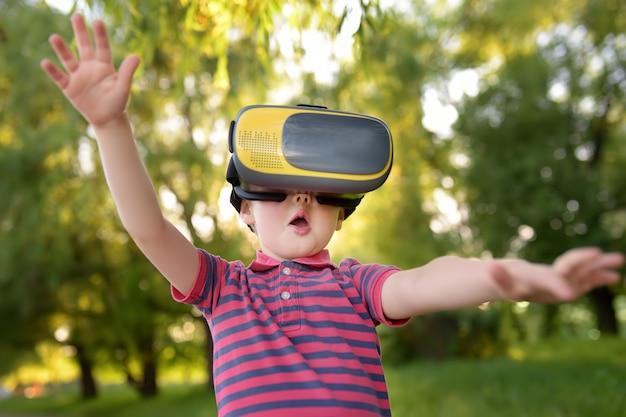 Ragazzino che usando la cuffia avricolare di realtà virtuale all'aperto