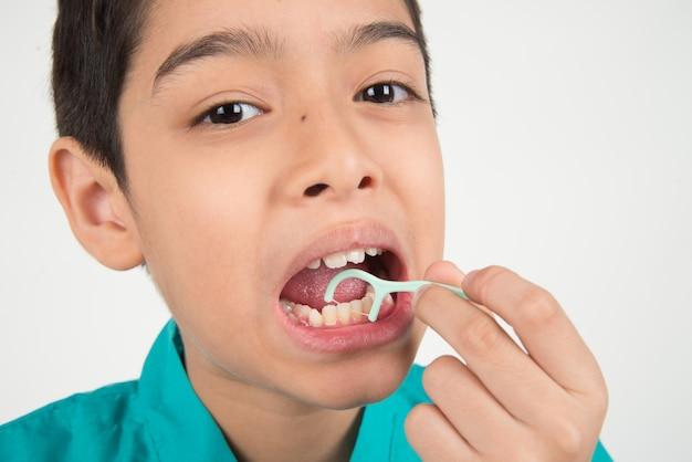 Ragazzino che utilizza il filo interdentale per pulire il dente