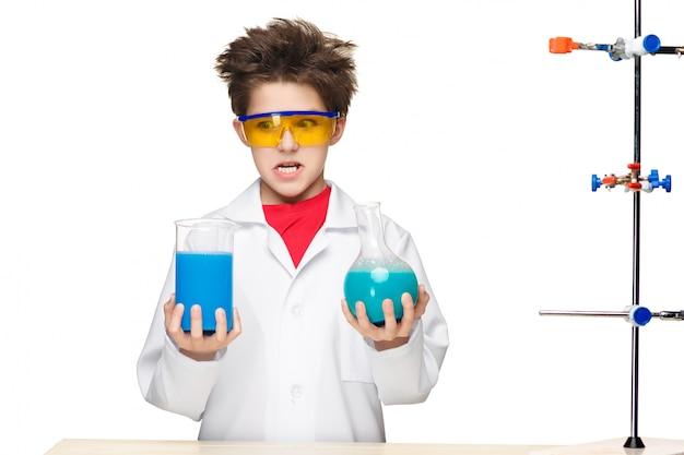 Ragazzino come chimico che fa esperimento con liquido chimico in laboratorio