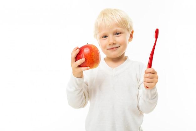 Ragazzino con capelli biondi corti, occhi azzurri, aspetto carino, in giacca bianca, pantaloni azzurri, si leva in piedi con una grande mela rossa e spazzolino rosso in mano