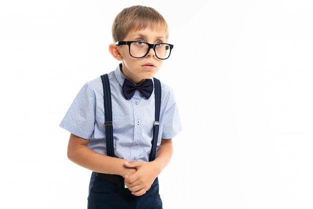 Ragazzino con gli occhiali neri con sedie trasparenti, camicia blu, pull-up molto insicuro