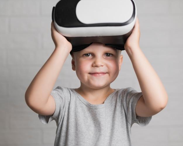 Ragazzino con l'auricolare virtuale acceso