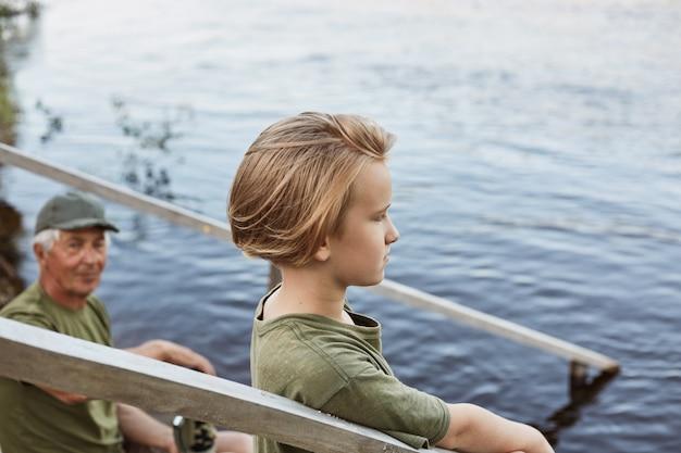 Ragazzino con vista misteriosa guardando in lontananza, ragazzo con il nonno in posa sulle scale in legno, famiglia trascorrere del tempo insieme all'aria aperta, godendo della splendida natura.