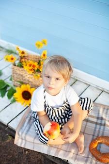 Ragazzino dai capelli biondi carino con una mela e un panino in mano sotto il portico di una casa di campagna in legno in una giornata d'autunno. vacanze estive, attività ricreative all'aperto. concetto di infanzia. picnic (pranzo)