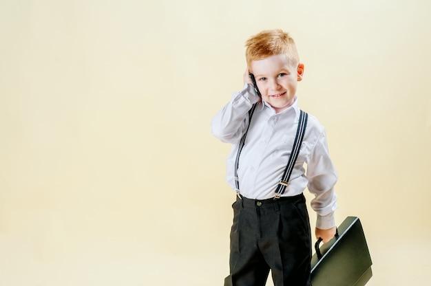 Ragazzino dai capelli rossi in un tailleur con un telefono in mano si affretta a una riunione in tailleur, affari, mini capo