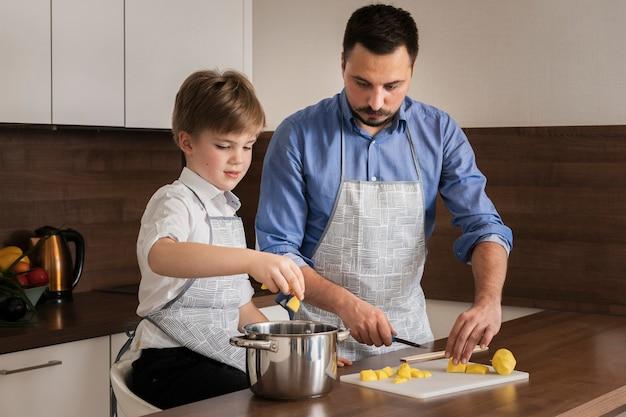 Ragazzino dell'angolo alto che aiuta suo padre a cucinare