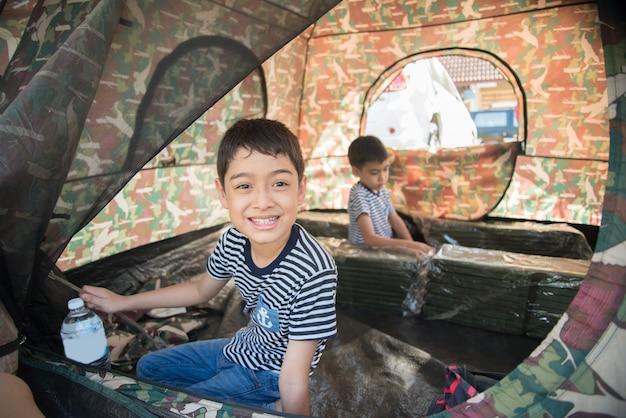 Ragazzino dentro la tenda che si accampa attività all'aperto di ora legale