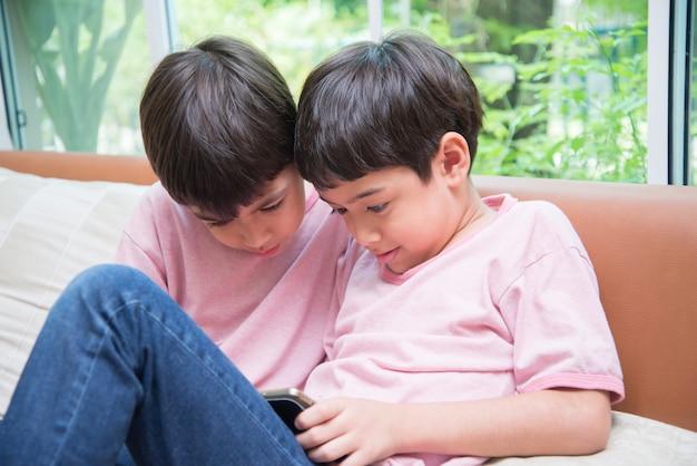Ragazzino di pari livello che gioca tablet a casa