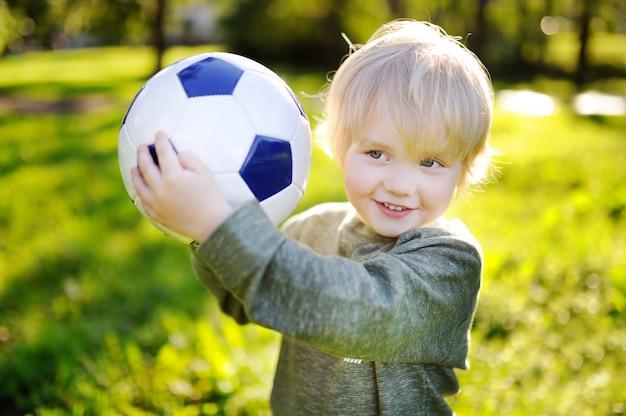 Ragazzino divertendosi a giocare una partita di calcio soleggiata giornata estiva