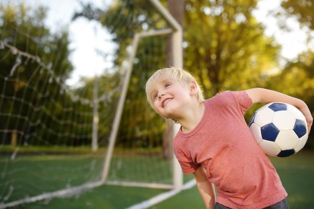 Ragazzino divertendosi giocando un calcio / partita di football americano il giorno di estate.