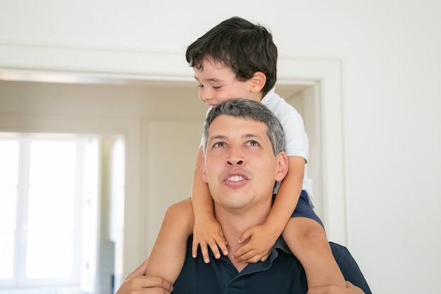 Ragazzino divertente che si siede sul collo di papà e sorridente.