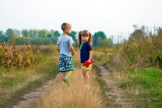 Ragazzino e bambina che giocano fuori sulla strada della ghiaia del campo un giorno di estate soleggiato