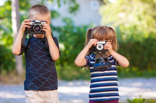 Ragazzino e ragazza che imparano come usare la macchina fotografica