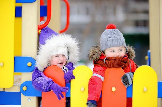 Ragazzino e ragazza in abiti invernali divertirsi nel parco giochi all'aperto
